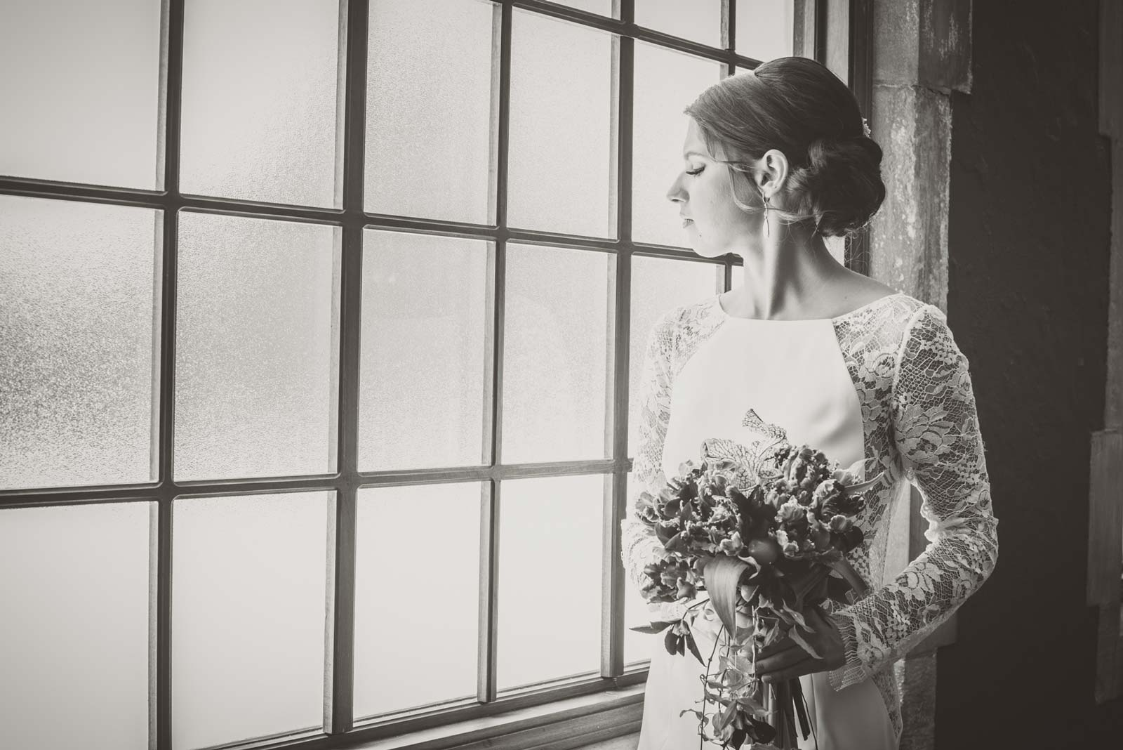 Black and White Photo of Bride in Window