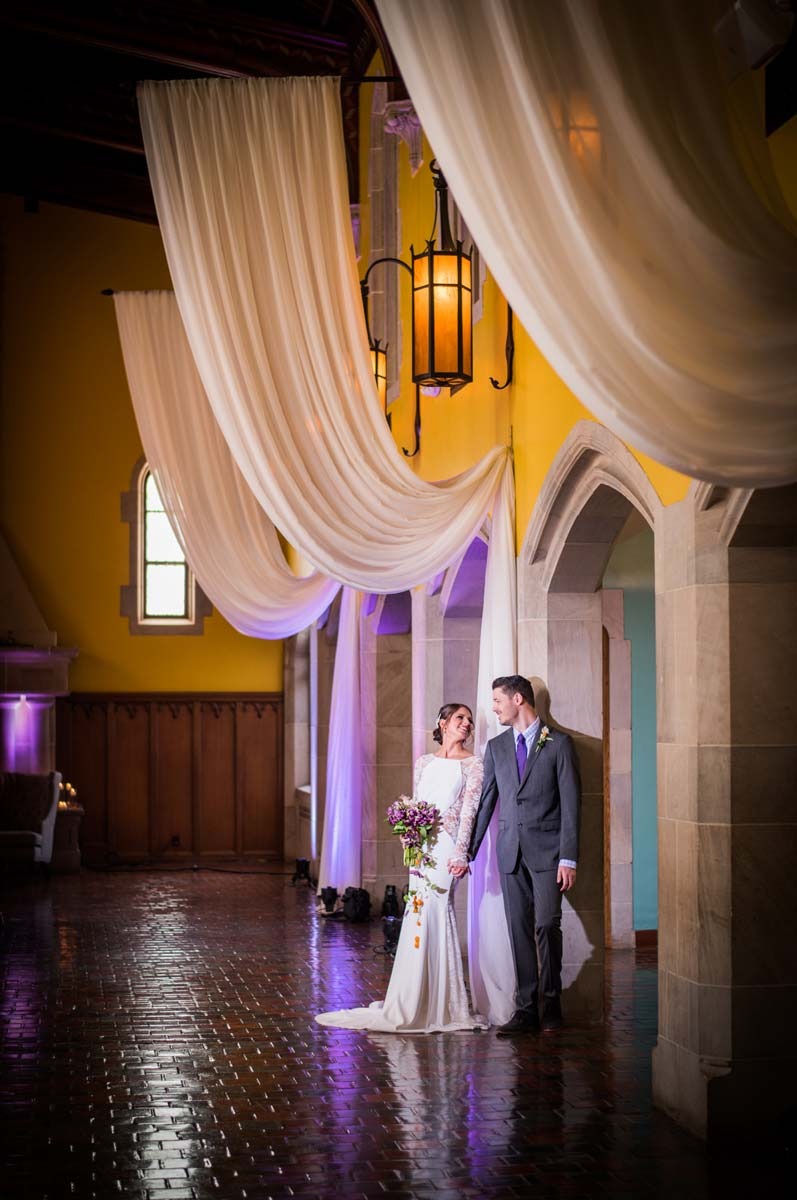 Bride and Groom with dramatic backdrop draping and uplighting