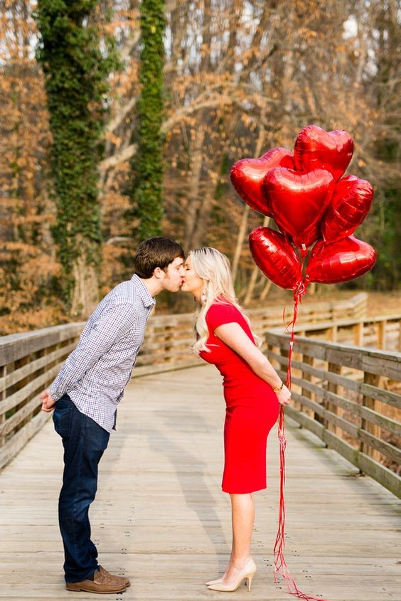A newly engaged couple kissing on a bridge holding red heart balloons